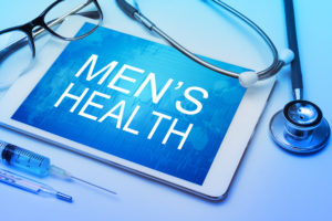 Men's health word on tablet screen with medical equipment on background